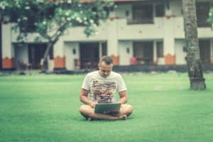 Man Using Laptop While Sitting On Lawn