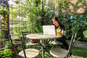 Woman Using Her Laptop In A Green Environment